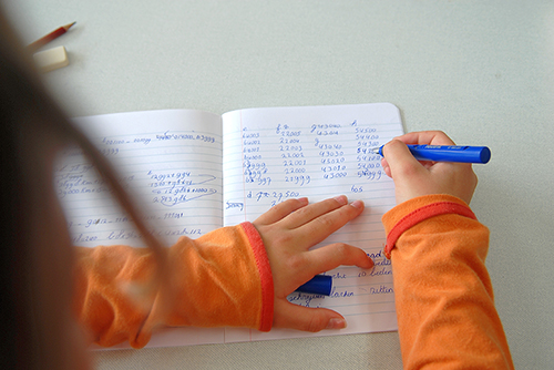 child writing on a red notebook